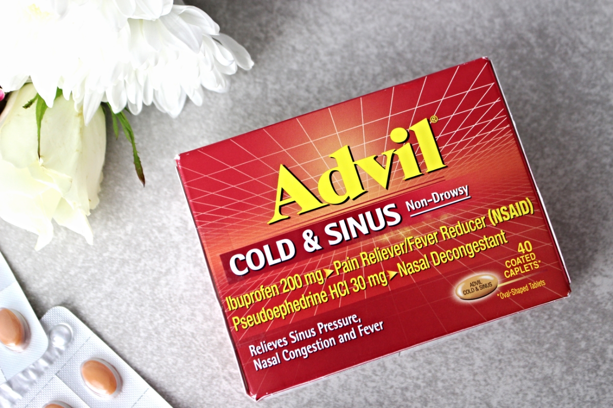 This is a close up shot of the Advil Cold and Sinus box and a plethora of flowers.
