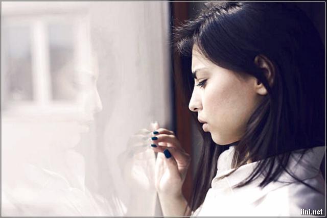 người đàn bà buồn nhìn ra cửa sổ