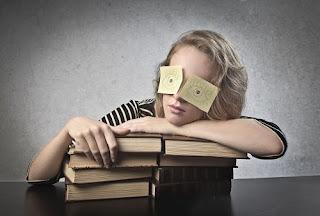 Joven apoyada sobre una pila de libros, con los ojos cerrados y dos papeles sobre los párpados donde se dibujan sus ojos.