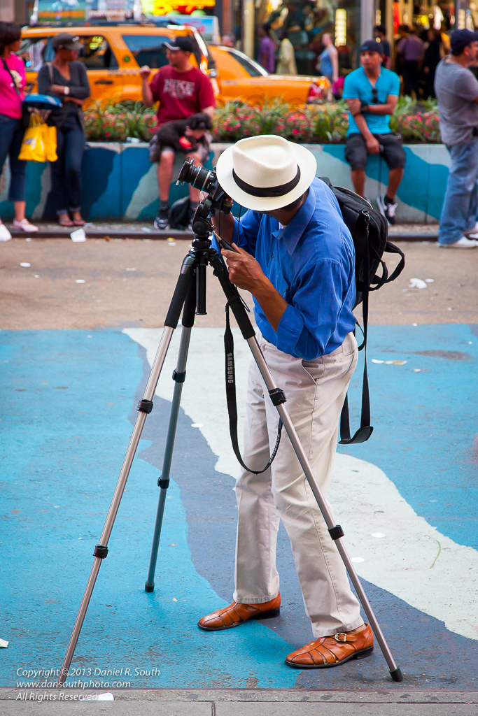 a photo of a photographer shooting with a tripod in times square