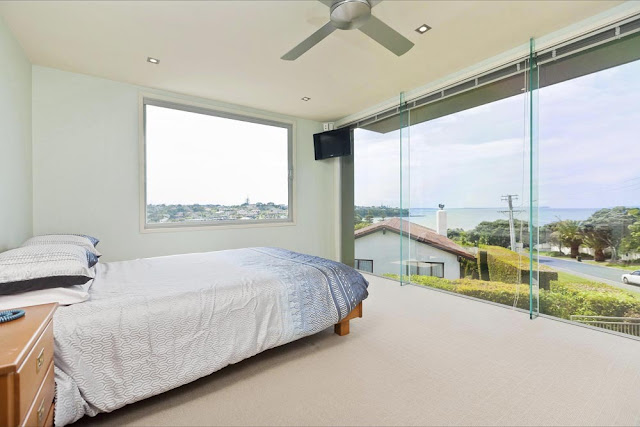 Photo of one of the bedrooms with glass wall facing the street