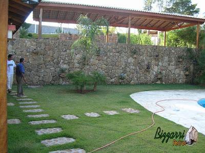 Muro de pedra bruta com os caminhos de pedra e a execução do paisagismo em residência em Mairiporã-SP.