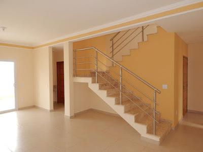 A escada com perfil aparente para as salas de estar e jantar, abriga uma despensa sob seu segmento mais alto, com acesso para a lavanderia. Este elemento promove também a ventilação por exaustão natural, dado que há uma abertura no pavimento superior para tanto.