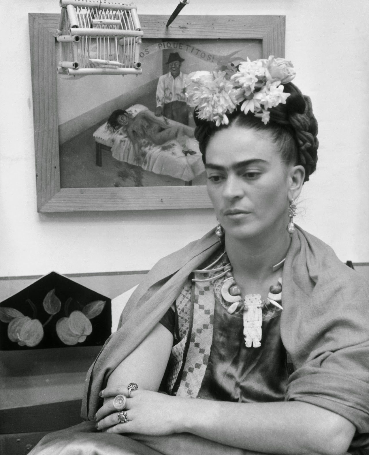 Frida kahlo sits with her arms folded looking down in front of one of her paintings and a wooden bird cage c 1945