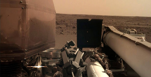 The Instrument Deployment Camera (IDC), located on the robotic arm of NASA's InSight lander, took this picture of the Martian surface on Nov. 26, 2018, the same day the spacecraft touched down on the Red Planet. The camera's transparent dust cover is still on in this image, to prevent particulates kicked up during landing from settling on the camera's lens. This image was relayed from InSight to Earth via NASA's Odyssey spacecraft, currently orbiting Mars. Credits: NASA/JPL-Caltech