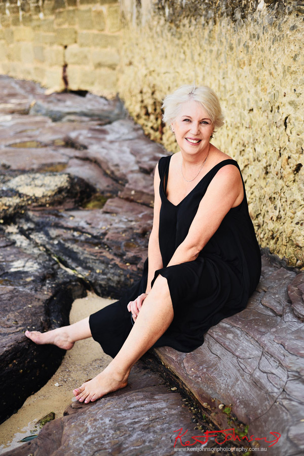 Seated on the rocks by the shoreline; an age positive modelling portfolio. Photography by Kent Johnson Sydney, Australia.
