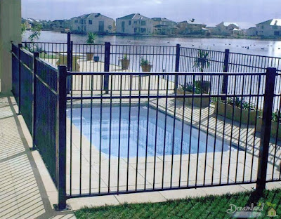A backyard tubular steel pool fence