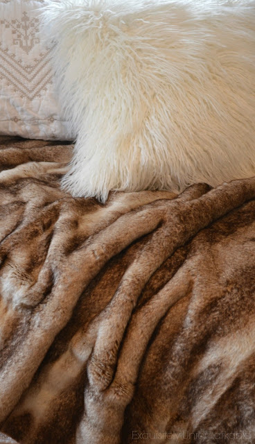 Fur blanket and pillow on a bed