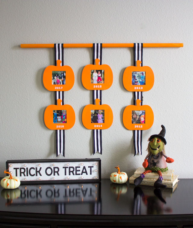 A fun way to display photos of your kids' Halloween costumes over the years! #halloweenphotodisplay #halloweenphotos #halloweencostumes
