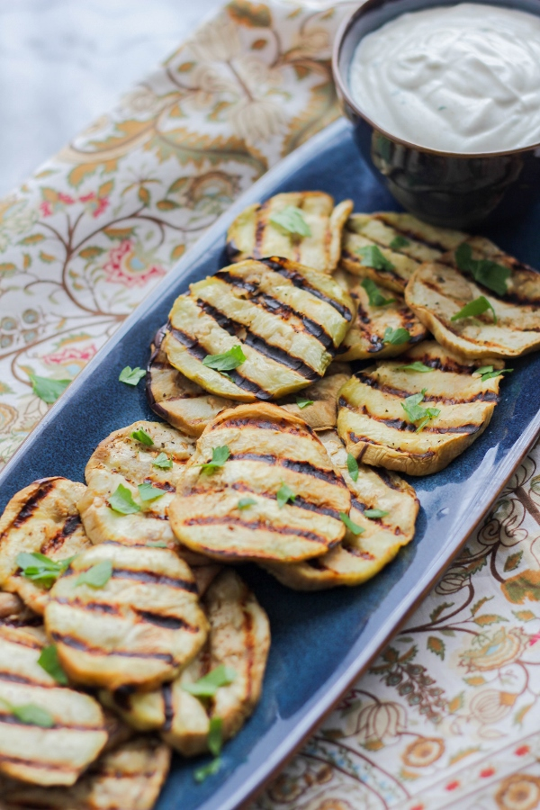 Thick eggplant slices are grilled to tender perfection and served with a creamy and delicious yogurt sauce. This simple recipe makes a perfect side dish or a great party appetizer!