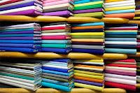 Bir manifatura dükkanındaki raflarda dizili renk renk kumaş topları