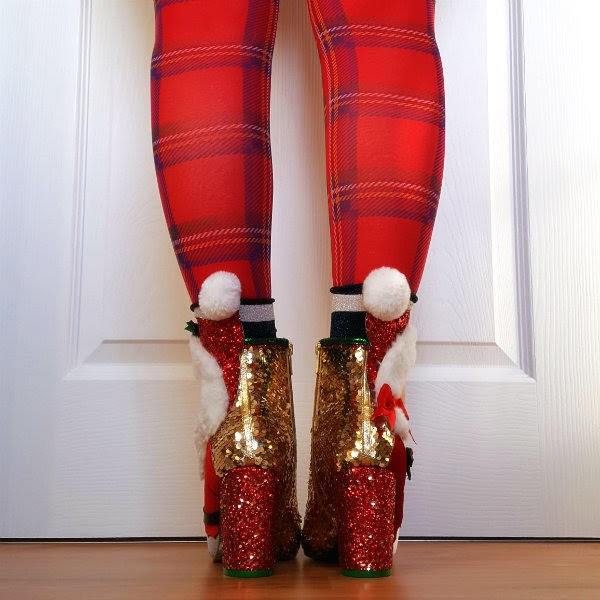 back view of legs wearing tartan tights and gold sequins ankle boots with white fluffy pom poms