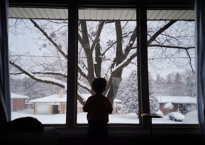 Toddler looking out the big window into the snow