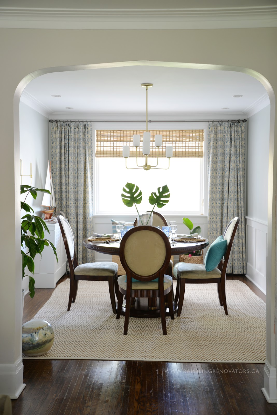 Ramblingrenovators.ca | tropical dining room, round dining table, gold chandelier, bamboo blind, naga blue curtain
