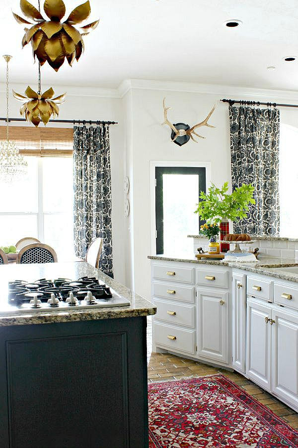 white kitchen cabinets, black island, brass hardware, lotus pendant light, vintage rug