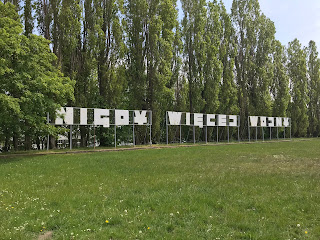 no more war in polish on a metal sign among some trees