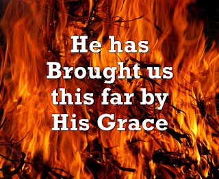 Song title superimposed on background of fire:    1 He has brought us this far by His grace, He has led us by fire and by cloud, He will bring us to Zion to look on His face, O blessed, O blessed be God.  Chorus Blessed be God, Blessed be God, Blessed, O blessed be God. 2 He has sheltered us under His wings, And He planned every path that we've trod. To bring us to Zion His praises to sing. O blessed, O blessed be God.