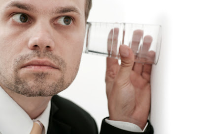 espionage spies man listening through wall with a glass