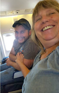 our son Tim sitting on an airplane, across the aisle from my wife Cindy
