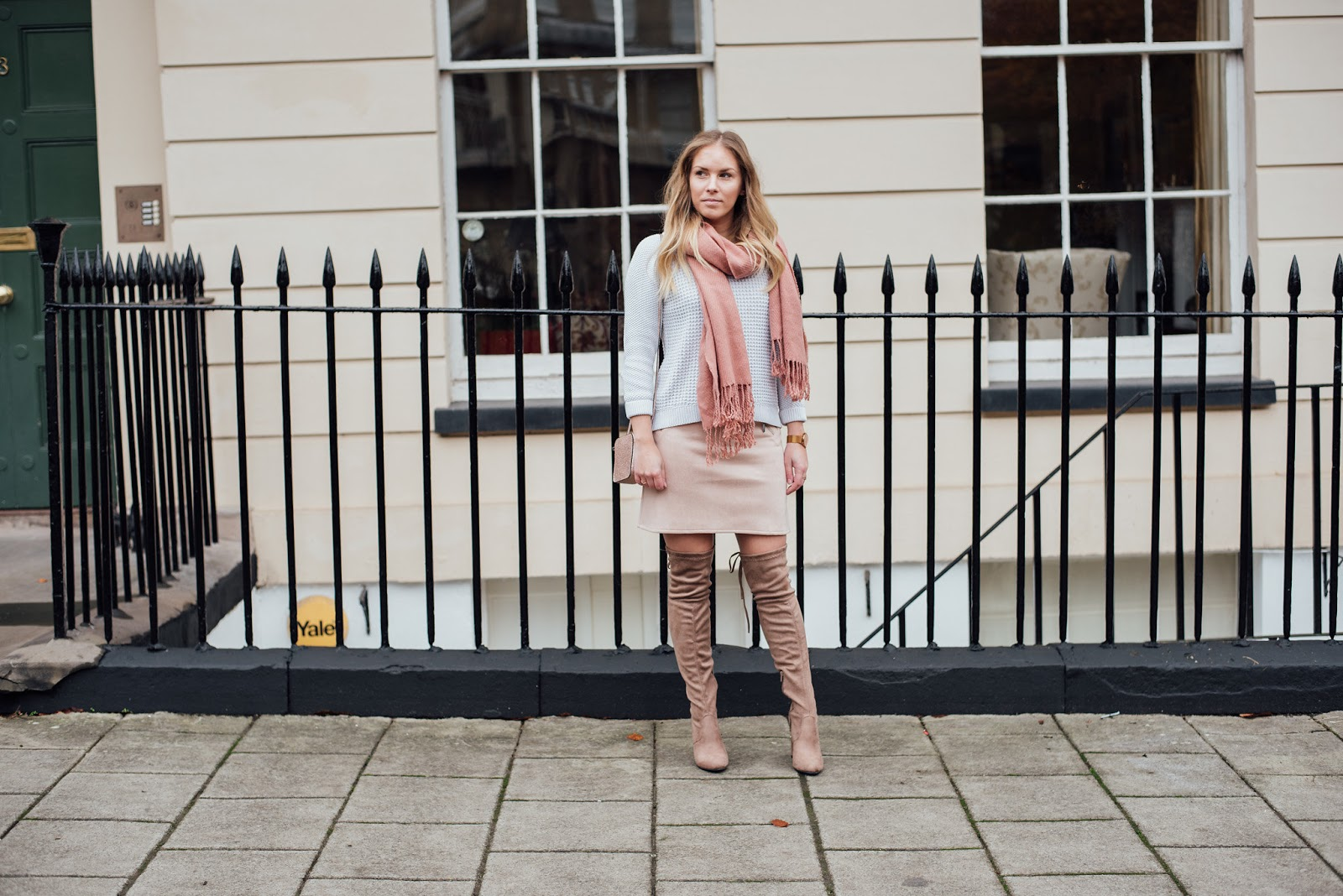 Rachel Emily wearing a pink scarf and suede skirt with a white chunky knit jumper and beige over the knee boots