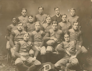 A photograph showing a group of men seated for a football team portrait.