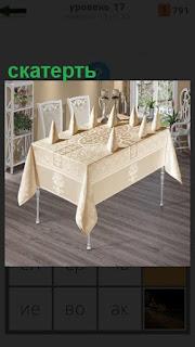 В помещении стоит стол, на котором накрыта скатерть и стоят салфетки