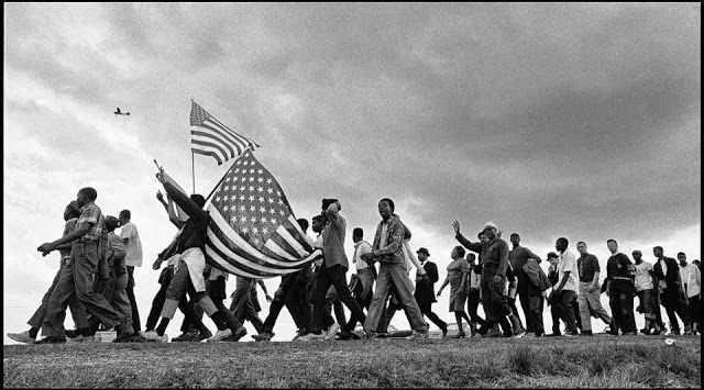 Photo of 1965 civil rights march Selma to Montgomery. Protesters carry two American flags and wave at a passing plane covering the march. Photo by Matt Herron.jpg