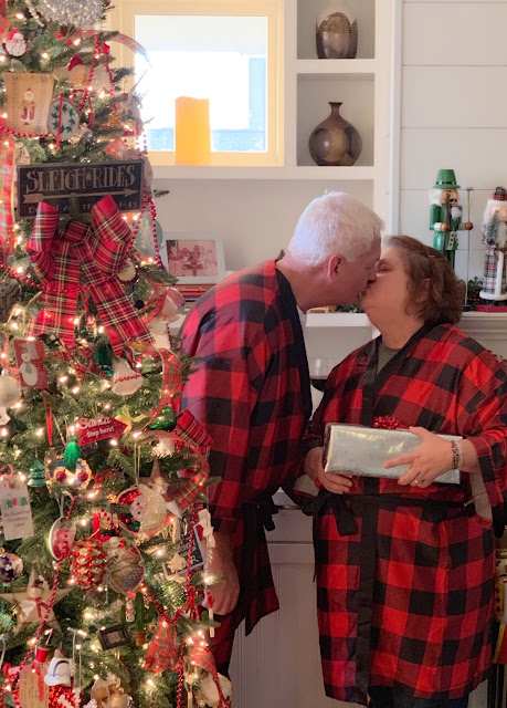 Christmas tree, man and woman kissing in matching buffalo plaid pajamas