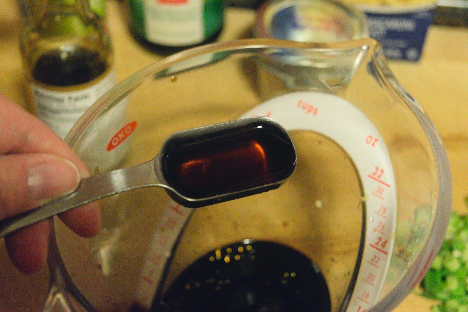 Sesame oil being added to the sauce in the measuring cup.