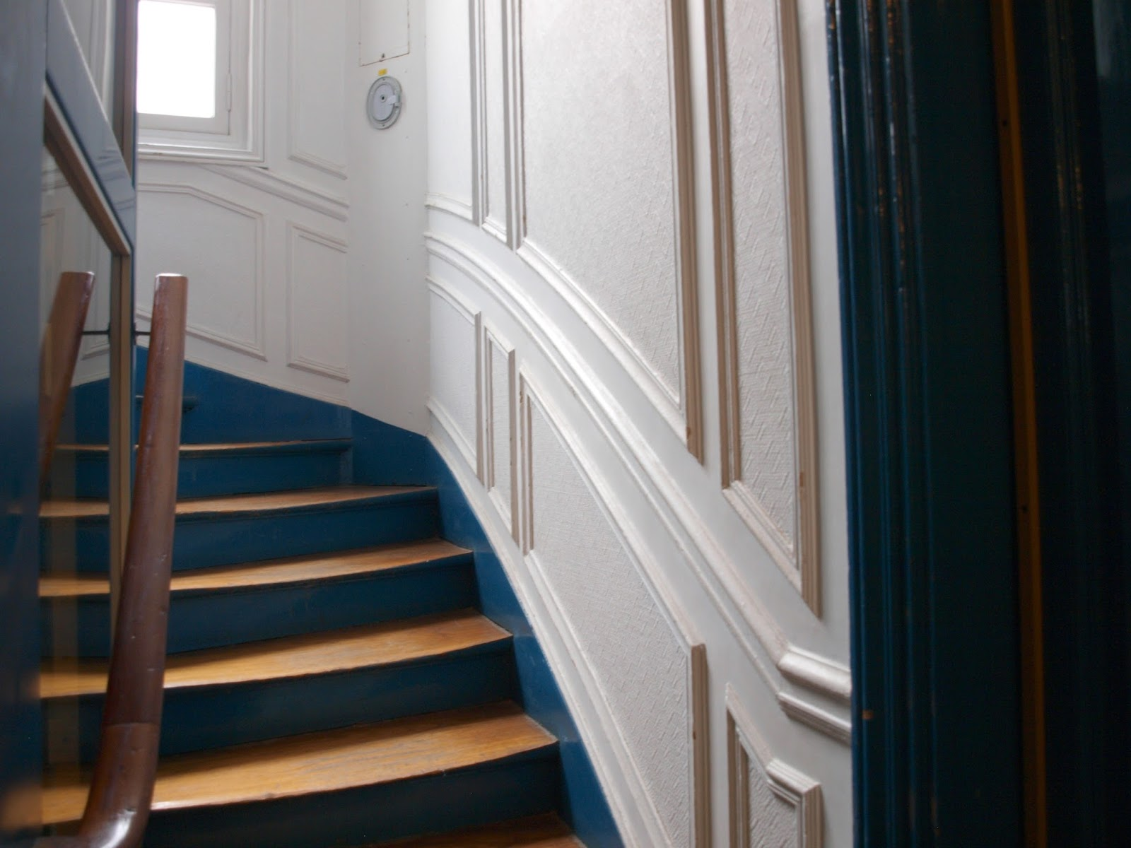 Beautiful white paneled wall in stairway to our Paris apartment - Hello Lovely Studio