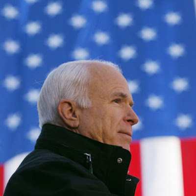 2008 photo of mcain looking off, behind an american flag.