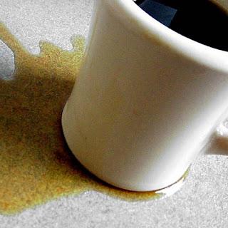 White cup of black coffee sitting in a spill on the table.