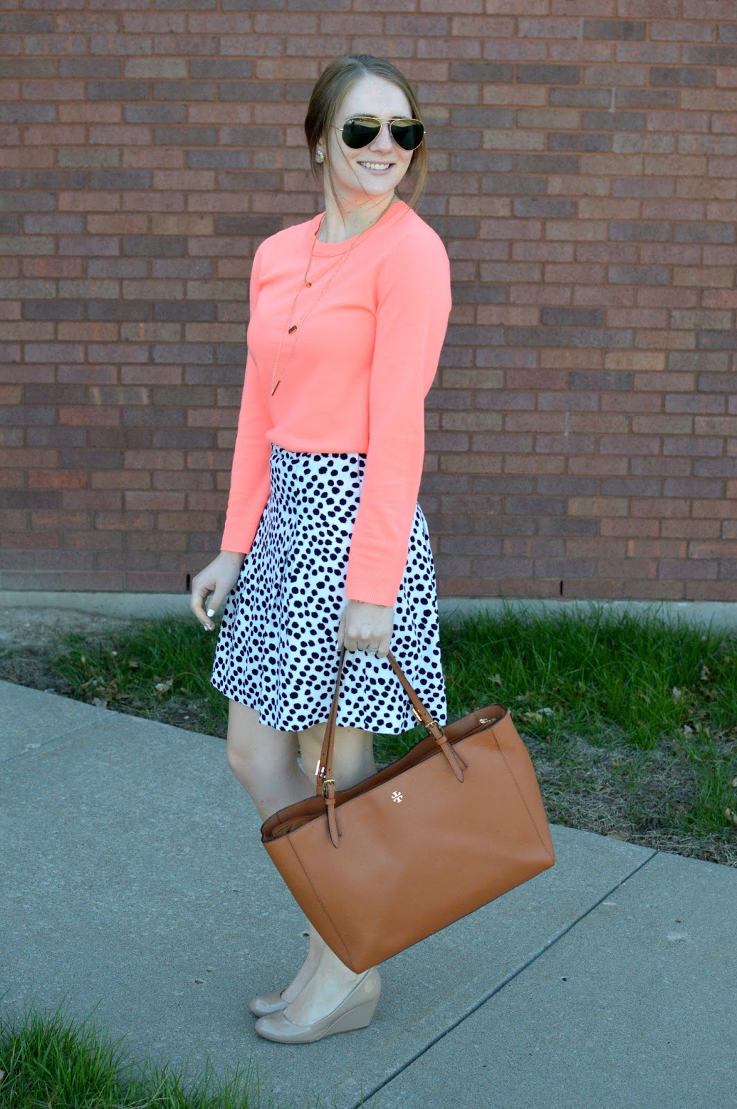 coral sweater with a black and white polka dot skirt for work