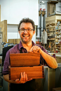 A happy man hold a box that he has made.