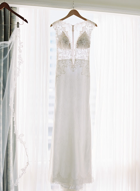 A wedding gown hanging in the window | Karen Hill Photography