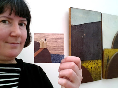 A woman holding up her collage in front of a work by Rosalie Gascoigne in The Daylight Moon exhibition.