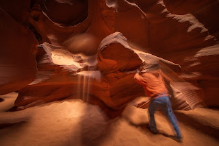 Navajo guide tosses handfuls of sand over rock in Upper Antelope Canyon.