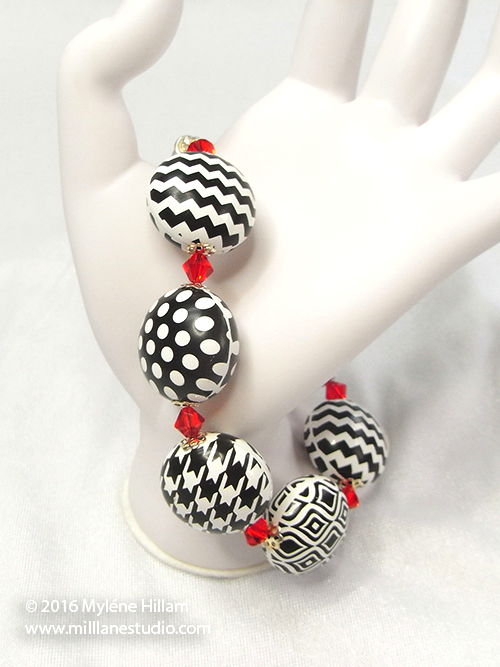 Black and white bracelet featuring Houndstooth, Chevron and Polka Dot beads interspersed with red crystal beads.