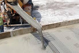beton ready mix sedang di tuangkan dibantu tenaga pekerja
