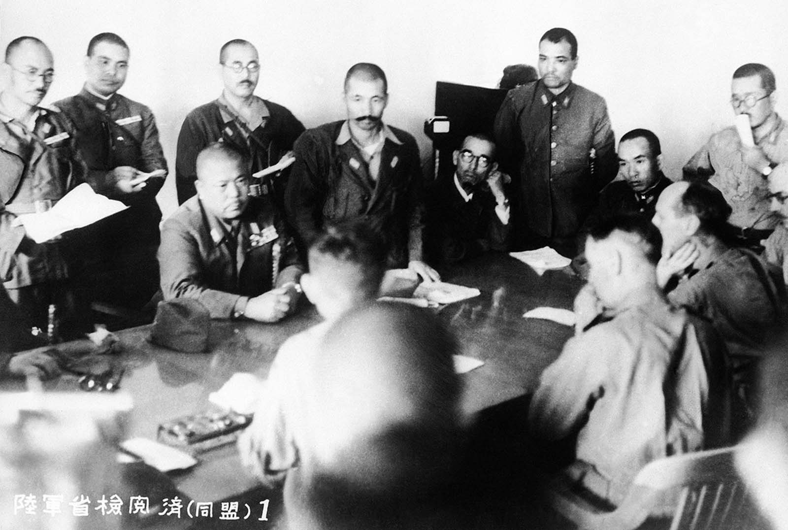 The conference at which Singapore surrendered on February 15, 1942. Man seated at left, facing camera, is identified as Lieut. Gen. Tomoyuki Yamashita, the Japanese Commander. Man in right foreground, profile to camera, is identified as Lieut. Gen. A. E. Percival, British commander.