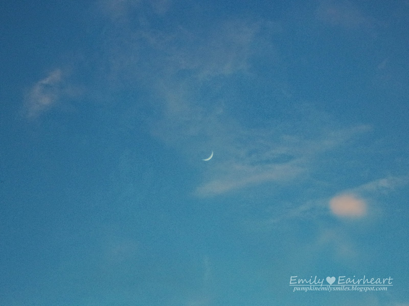 Crescent moon with pink clouds surrounding it.