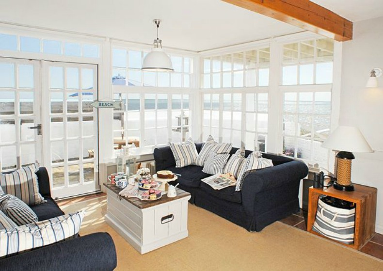 Coastal navy slipcover sofas and vast ocean view from this beach house living room