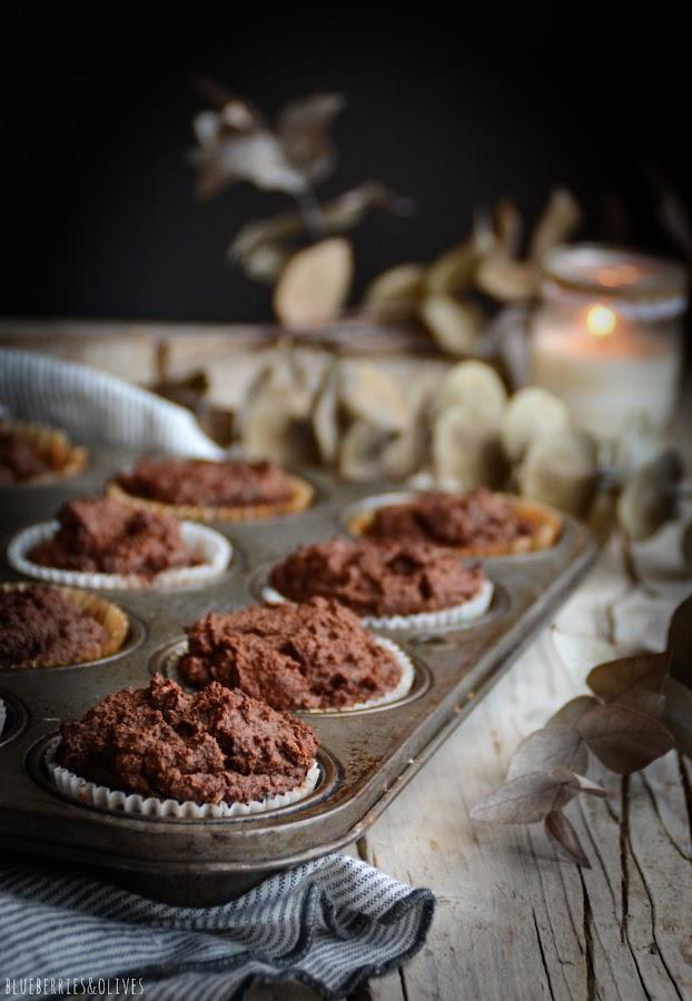 Dark mood muffins con fondo oscuro, ramas secas , vela encendida, mesa madera antigua