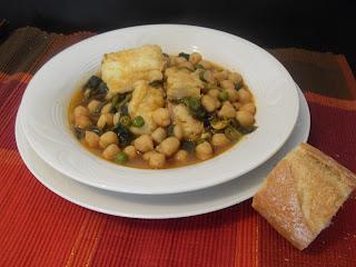 Plato de garbanzos con bacalao, espinacas y guisantes sobre la mesa