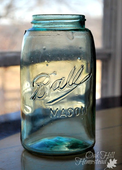 An antique green glass canning jar