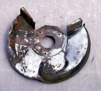 Image of an Opel Manta brake disc back plate on a grey background