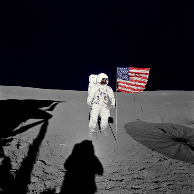 "Astronaut Edgar D. Mitchell, Apollo 14 lunar module pilot stands by the deployed U.S. flag on the lunar surface during the early moments of the mission's first spacewalk. He was photographed by astronaut Alan B. Shepard Jr., mission commander. While astronauts Shepard and Mitchell descended in the Lunar Module ""Antares"" to explore the Fra Mauro region of the moon, astronaut Stuart A. Roosa, command module pilot, remained with the Command and Service Module ""Kitty Hawk"" in lunar orbit. Credits: NASA"