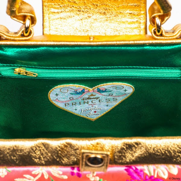 inside of handbag with green metallic lining and gold studs