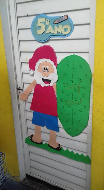 Decoração de porta natalina com Papai Noel surfista
