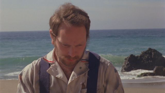 man looks sad on the beach. Probably because he found out he was in the film The Aftermath